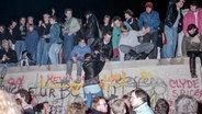 Menschen feiern am 10. November 1989 vor und auf der Mauer in Berlin den Mauerfall. © picture-alliance/ ZB Foto: Peter Zimmermann