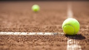 Eine Bodenansicht zweier Tennisbälle auf einem Tennisplatz. © fotolia.com Fotograf: Sebastian Duda