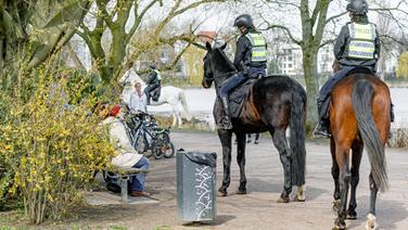 Berittene Polizisten sprechen mit Menschen in einem Park an der Hamburger Außenalster. | dpa-Bildfunk