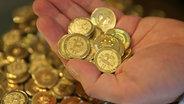 Mehrere goldene Münzen in einer Hand. © dpa picture alliance Fotograf: George Frey