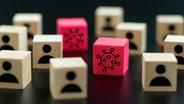 Diverse Holzwürfel, auf denen Männchen gedruckt sind, auf zwei roten ist eine Corona-Virus-Symbol. © Colourbox