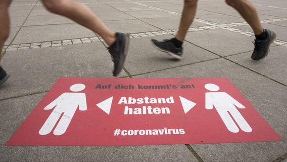 Eine Corona-Abstandsmarkierung auf dem Boden. © picture alliance Foto: Frank Rumpenhorst