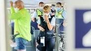 Mitarbeiter der DB Sicherheit und Beamte der Bundespolizei gehen durch einen Zug und kontrollieren, ob die coronabedingte Maskenpflicht eingehalten wird. © picture alliance Foto: Annette Ried