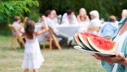 Im Vordergrund vor einer Gartenparty wird ein Teller mit Melone gezeigt. © imago-images Foto: ingimage
