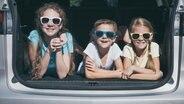 Drei Kinder mit Sonnenbrillen liegen im Kofferraum eines Autos. © photocase.de Foto: altanaka