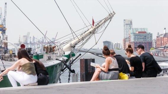 Junge Leute sitzen am Hamburger Hafen auf den Stufen. (Symbolbild) © picture alliance Foto: Markus Scholz