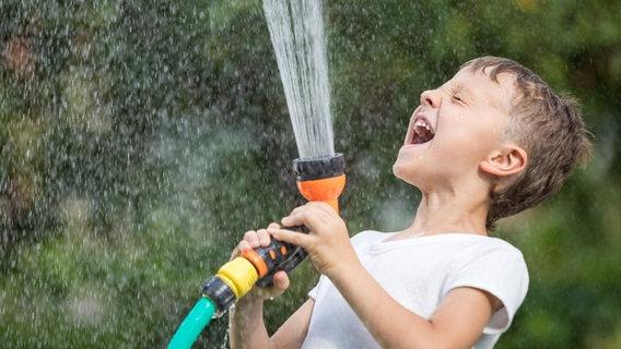 Ein Junge besprüht sich mit einer Gartendusche © photocase.de Foto: altanaka