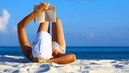 Frau liest am Strand ein Buch © Fotolia Foto: Malbert