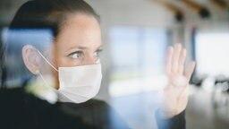 Eine junge Frau mit Maske an hinter einem Fenster © Colourbox