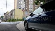 Ein Fahrzeug vom Ordnungsamt steht vor einem unter Quarantäne gestellten Wohnhaus. © dpa-Bildfunk Foto: Swen Pförtner/dpa