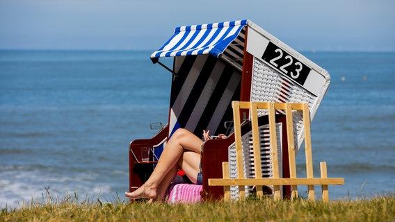 Eine Frau sonnt sich in ihrem Strandkorb am Meer. © dpa-Bildfunk Foto: Rolf Vennenbernd/dpa