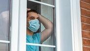 Ein Mann steht mit einem Mundschutz am Fenster © Colourbox