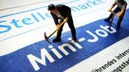 """Spielzeugpuppen """"arbeiten"""" auf einer Mini-Job-Anzeige. © dpa Foto: Frank Rumpenhorst"""