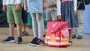 Schulkinder mit stehen wartend in einer Reihe. © picture alliance Foto: Mascha Brichta