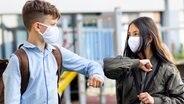 Zwei Teenager-Schüler mit Schutzmasken begrüßen sich mit einem Ellenbogen-Kick. (Themenbild) © Colourbox Foto: -