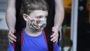 Ein Schüler mit Schutzmaske steht vor seiner Mutter bei der Einschulung. © picture alliance Foto: Brynn Anderson