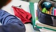 Eine rote Schutzmaske liegt auf einem Schultisch. © picture alliance Foto: Marijan Murat
