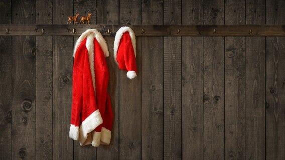 Ein Weihnachtsmann- Kostüm hängt an einer Garderobe aus Holz. © fotolia.com Fotograf: Springfield Gallery