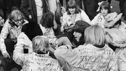 Beatles-Fans sitzen am 26.10.1965 vor dem Buckingham Palast in London. © dpa/picture alliance