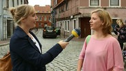 NDR Info Reporterin Bettina Less (links) interviewt eine junge Frau. © Screenshot