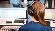 Eine Frau mit langen braunen Haaren und aufgesetzten Kopfhörern sitzt vor einem Moderationspult mit vielen Knöpfen, Reglern, Bildschirmen und einem Mikrofon.