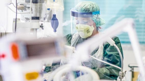 Eine Krankenpflegerin arbeitet in Schutzkleidung in einem Krankenzimmer auf der Intensivstation. © picture alliance/dpa Foto: Marcel Kusch