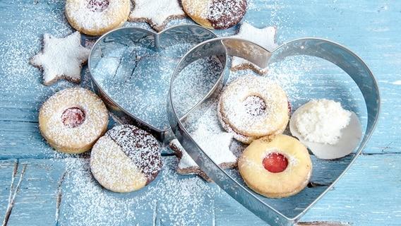 Weihnachtliche Kekse mit herzformigen Backformen auf blauem Holzhintergrund. © fotolia.com Fotograf: doris oberfrank-list