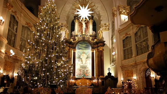 Ein geschmückter Tannenbaum steht bei einer Krippenandacht in der Hauptkirche St. Michaelis in Hamburg. © picture alliance/dpa Foto:  Malte Christians