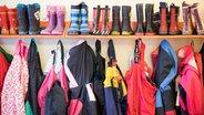 Bottes et vestes en caoutchouc sur une garde-robe de maternelle. © photo alliance / dpa photo: Christian Charisius