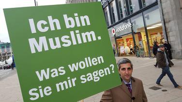 Michel Abdollahi mit einem Schild, auf dem steht: Ich bin Muslim. Was wollen Sie mir sagen? © NDR / Stefan Mühlenhoff