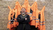"Ai Weiwei steht vor seinem Kunstwerk ""Safety Jackets Zipped the Other Way"" © picture alliance/Christoph Soeder/dpa Foto: Christoph Soeder"