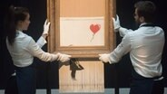 "Zwei Mitarbeiter des Auktionshauses Sotheby's halten das halb-geschredderte Banksy-Bild ""Girl with Balloon, 2018"" in die Höhe. © picture alliance / Photoshot"