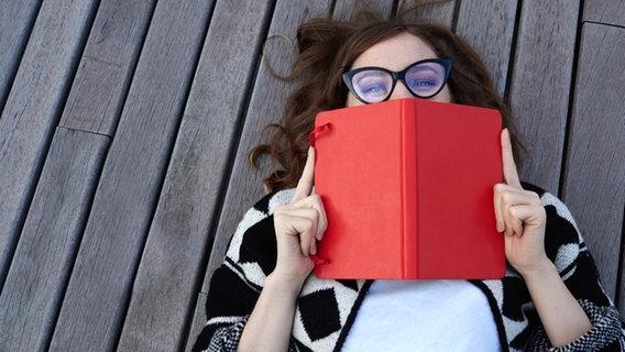 Eine Frau, die auf einem Holzsteg liegt, hält sich ein Buch vor Mund, Hals und Nase. © fotolia.com Foto: pintorama