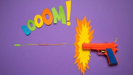 Eine Spielzeugpistole mit aus bunten Papier gebastelten Comic-Elementen. © photocase Foto: complize