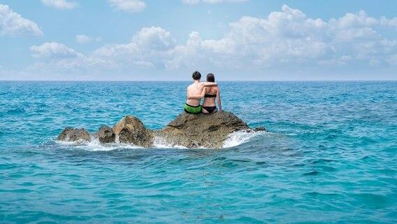 Ein Paar sitz auf einem Felsen im Meer. © photocase Foto: Armin Staudt