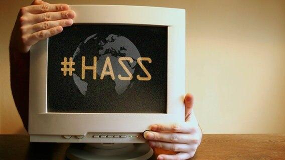 """Ein Monitor, der von Händen umgriffen wird mit der Aufschrift """"#Hass"""" und einer Weltkugel. © photocase, fotolia Foto: spacejunkie, senoldo"""