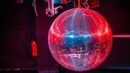 Eine Discokugel wird von rote Licht angestrahlt. © picture alliance/Jens Büttner/dpa-Zentralbild/ZB Foto: Jens Büttner