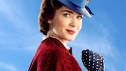 "Eine junge Frau mit rotem Hut und blauem Cape steht vor einer Tür - Szene aus ""Mary Poppins Returns"" von Rob Marshall mit © 2017 Disney Enterprises, Inc. All Rights Reserved. / Jay Maidment"