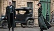 """Zwei menschen stehen vor einem alten Auto - Szene aus Phantastische Tierwesen: Grindelwalds Verbrechen""""Johnny Depp als Gellert Grindelwald (links) © 2017 WARNER BROS. ENTERTAINMENT INC Foto: Mark Seliger"""