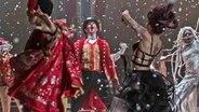 """Hugh Jackman tanzt im roten Frack mit Zylinder zwischen Frauen auf der Bühne - Szene aus dem Film-Musical """"Greatest Showman"""" © 2017 Twentieth Century Fox"""