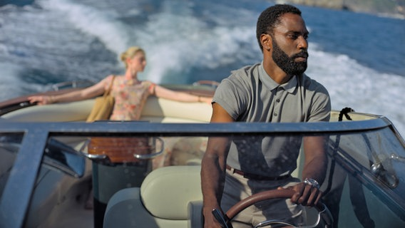 "John David Washington (rechts) am Steuer eines Schnellbootes und Elizabeth Debicki als Passagierin - Szene aus dem Film ""Tenet"" von Christopher Nolan © 2020 Warner Bros. Entertainment, Foto: Melinda Sue Gordon"