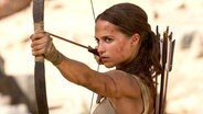 "Eine junge Frau mit zurückgebundenen Haaren spannt einen Bogen und zielt - Alicia Vikander als Lara Croft im Film ""Tomb Raider"" ©  2017 WARNER BROS. ENTERTAINMENT INC. AND METRO-GOLDWYN-MAYER PICTURES INC Fotograf: Ilze Kitshoff"