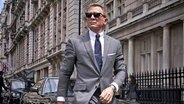 "Daniel Craig mit Sonnenbrille im grauen Anzug in London im neuen James-Bond-Thriller ""No Time To Die"" © DANJAQ LLC and MGM"