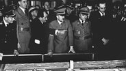 Adolf Hitler (M) am Modell der Volkswagenfabrik © Picture-Alliance/dpa