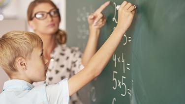 Ein Junge und eine Lehrerin rechnen an einer Tafel. | fotolia