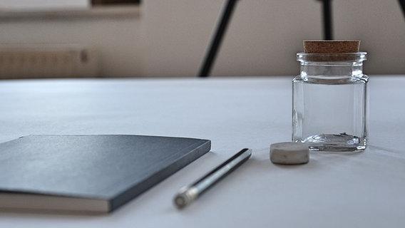 Auf einem Tisch liegen ein Heft, ein Stift - daneben steht eine kleine, leere Glasflasche. © NDR Fotograf: Jette Studier