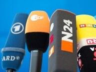 Mikrofone verschiedener Sender stehen auf einem Tisch. © dpa Foto: Soeren Stache