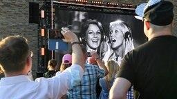 """Beim Abba-Event """"Abba Voyage"""" im Hotel """"nhow Berlin"""" verfolgen zahlreiche Fans die Ankündigung von ABBA, dass ein neues Album und eine Hologramm-Show kommen wird. © dpa-Zentralbild/dpa Foto: Jens Kalaene"""