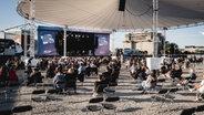Das Publikum sitzt auf Klappstühlen beim Konzert. © NDR Foto: Benjamin Hüllenkremer