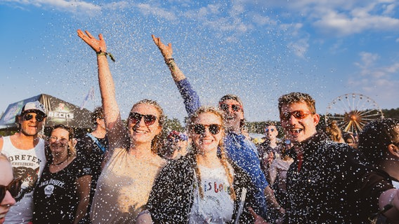 Besucher des Hurricane Festivals werfen Konfetti.  Foto: Benjamin Hüllenkremer